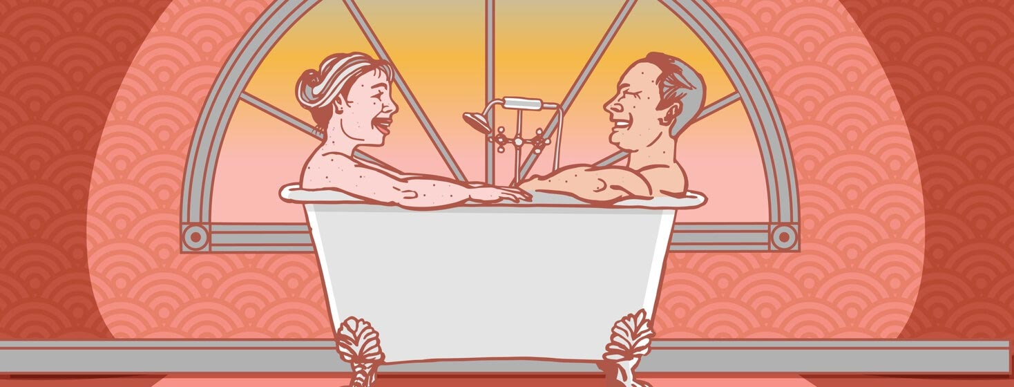 a couple sit in a tub laughing
