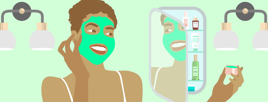 a woman applies a green face mask and looks at herself in a medicine cabinet, which is open to reveal all of her other products