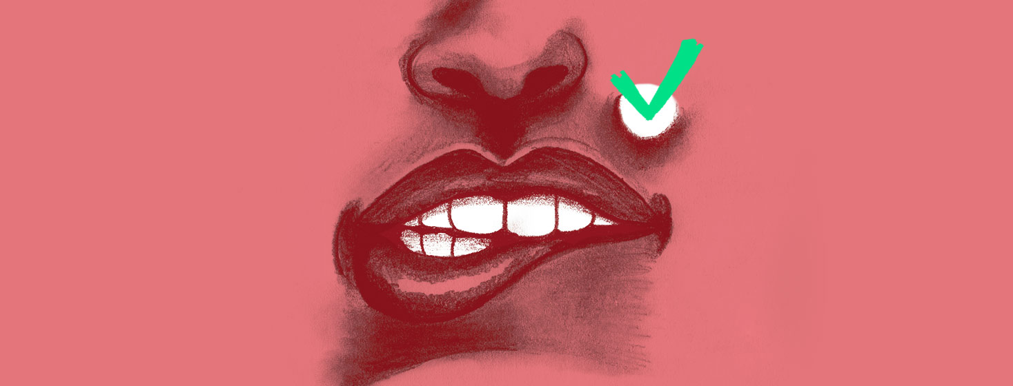 close up of teeth biting a lower lip and a green check mark on a white spot on the upper lip