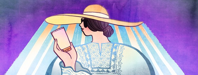 A woman holds a bottle of sunscreen in one hand, as her wide-brimmed hat and long-sleeved shirt protects her from harmful UV rays.