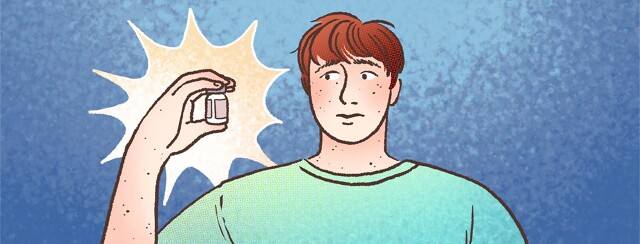 A redheaded man holds a bottle of anesthetic drug with a skeptical expression.