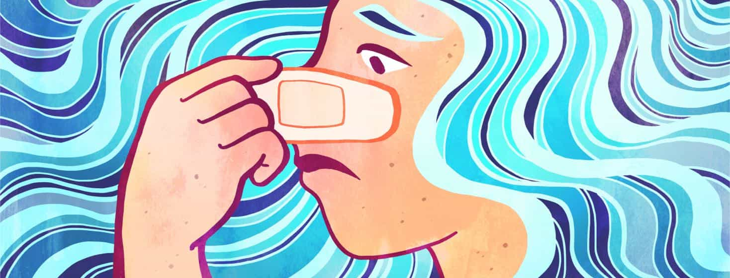A woman touches a bandage on her nose.